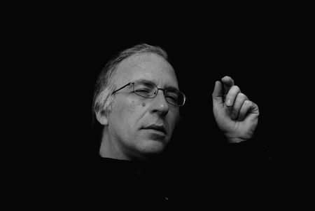 squinting: man squinting and gesturing with hand in this three quarter view portrait with dark background Stock Photo
