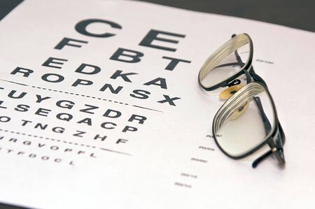 heathcare: modern eyeglasses resting on eyechart at an angle with frame closed Stock Photo