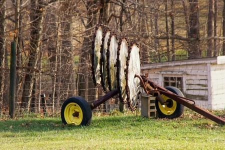 baler: hay baler blades resting on trailer in farm near woods