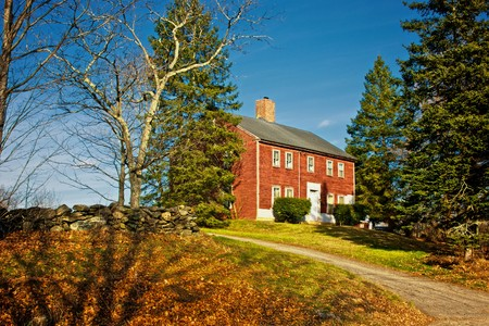 old red colonial house up on hill in nottingham new hampshire on a fall afternoon photo
