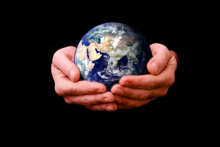 composite: compuesto imagen de hombre con el planeta tierra en su mano ahuecada contra un fondo negro Foto de archivo