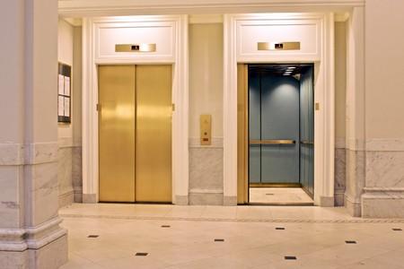 1 階にツイン エレベーターに直面して、1 つは開いています。 写真素材