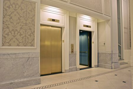 looking at twin elevators on first floor, one is open Stock Photo