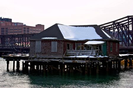 falling apart: old falling apart dock house at the edge of boston harbor Stock Photo