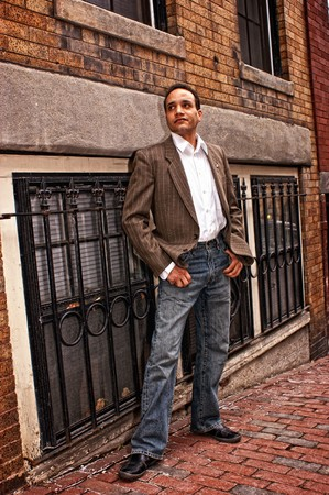 african american male posing on the sidewalk  wearing dress shirt , suit coat, blue jeans looking up street in beacon hill boston massachusetts photo