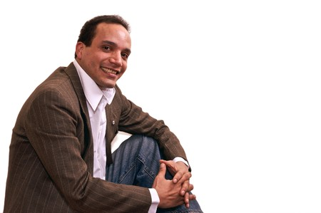 sitting and smiling portrait of african american male wearing dress shirt , sports coat and blue jeans against white background photo