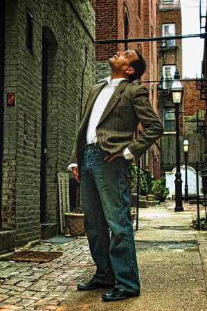 1 person: ethnic american male standing in alleyway, looking up wearing suit jacket, dress shirt and blue jeans,  in boston massachusetts