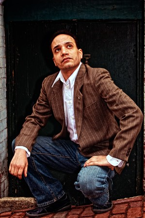 ethnic american male squatting in front of doorway wearing suit jacket, dress shirt and blue jeans, looking up from brick sidewalk in boston massachusetts photo