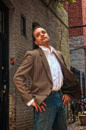 ethnic american male standing in alleyway, head tilted, with hands on hips looking down his nose at viewer wearing suit jacket, dress shirt and blue jeans,  in boston massachusetts photo