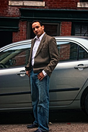ethnic american male giving sideways glance in front of silver car wearing suit jacket, dress shirt and blue jeans,  in boston massachusetts photo