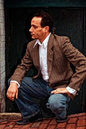 ethnic american male squatting in front of doorway wearing suit jacket, dress shirt and blue jeans, looking  down street on brick sidewalk in boston massachusetts photo
