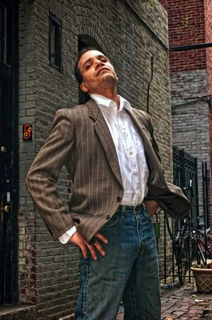gritty: ethnic american male standing in alleyway, head tilted, with hands on hips looking down his nose at viewer wearing suit jacket, dress shirt and blue jeans,  in boston massachusetts