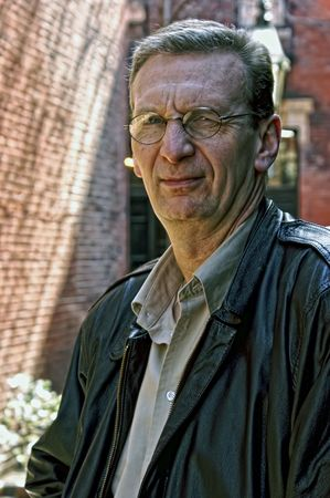 squinting: portrait of older man squinting outside wearing glasses and a leather jacket