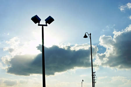 light posts silhouette against a blue sky with clouds hiding the sun Imagens