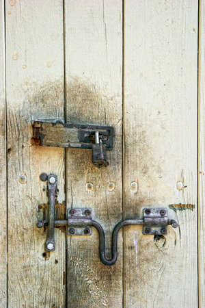 hasp: old painted wooden dirty door with rusted lock and hasp