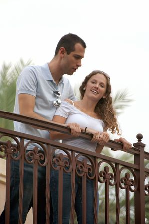 young lovers looking down from outside balcony on an overcast afternoon making the light soft with palm trees in the background