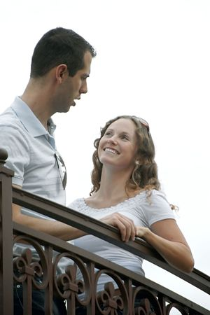 beautiful young couple talking and smiling on outside balcony . shot on an overcast day from a low angle making the sky look white Фото со стока
