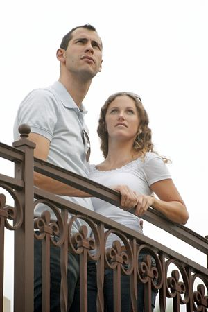 humourous image of young couple looking up to the sky from outside balcony as if they just spotted a ufo their hands touching. shot on an overcast day making the sky look white photo