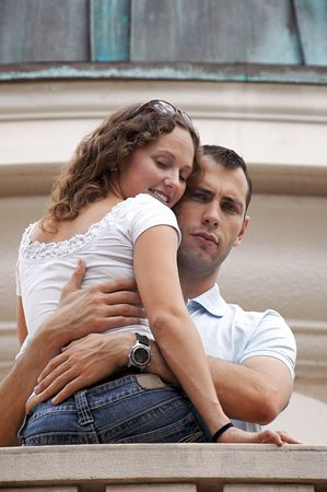 beautiful happy curly haired woman being embraced by serious man on balcony. shot on overcast day providing soft lighting