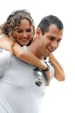 beautiful curly haired smiling woman with arms wrapped around the shoulders of happy handsome man both looking down. shot on overcast day providing soft lighting and making the sky appear whitish Banco de Imagens