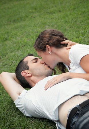 cut grass: beautiful image of young lovers  laying on the grass kissing in the park Stock Photo