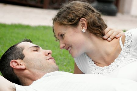 romantic image of beautiful couple smiling at each other laying on the grass in the park Stock Photo - 4889631