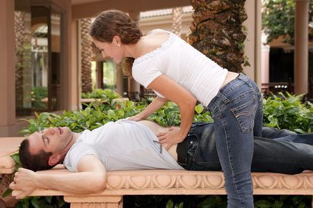 attractive young lady getting ready to massage her mans chest at tropical resort