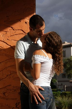 affairs: beautiful sexy young lovers kissing in the hot afternoon sun up against a wall in romantic tropical setting with heavy shadows and vibrant colors