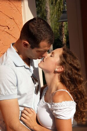 beautiful young couple holding each other about to kiss in the hot afternoon sun outside in tropical setting Stock Photo
