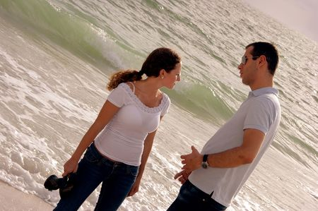 young couple at the beach in the gulf of mexico having a serious discussion, she is looking away with waves crashing behind them. photo