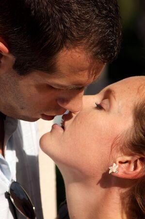 besos apasionados: cerca de la hermosa joven pareja con sus labios a punto de parted beso caliente en la tarde de Domingo