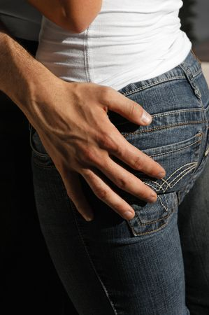 man resting his hand on woman's hip she is wearing tight jeans outdoors in the hot afternoon sunshine