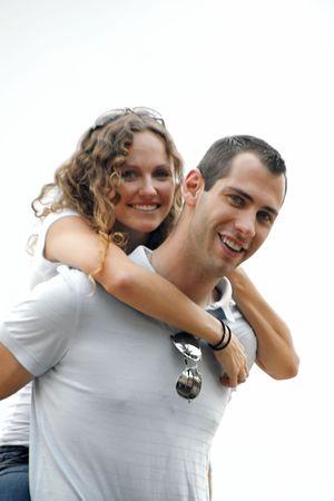 뷰어 향해 찾고 행복 잘 생긴 남자의 어깨 주위에 래핑 된 아름다운 곱슬 머리 웃는 여자. 부드러운 조명을 제공하고 하늘이 희끄무레하게 나타나는 흐