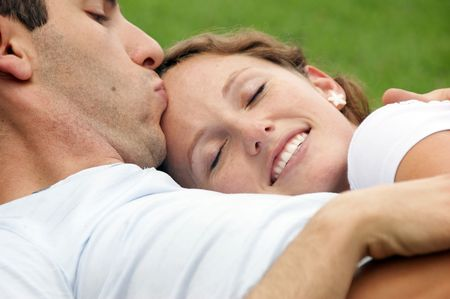 passionate couple: smiling woman with eyes closed resting her head on her husbands chest as he kisses her forehead