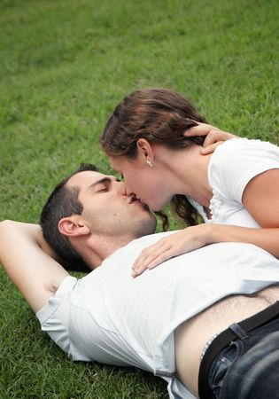 sweet image of young couple laying on the grass in a park  kissing
