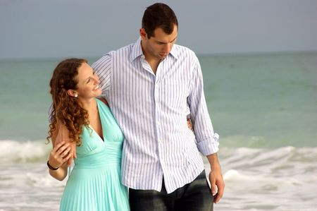 young couple walking along bonita beach in florida at the gulf of mexico having a discussion with waves crashing behind them. Woman is smiling and looking up at her man. Stock Photo