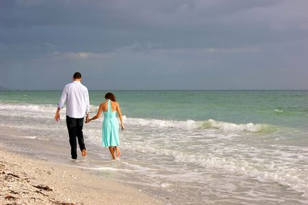 beautiful peaceful image of young couple walking along bonita beach in bonita springs florida on the gulf of mexico as the sun begins to set behind them photo