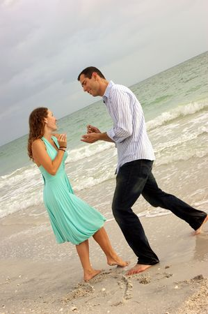 humorous image of beautiful young couple on beach pretending to propose on the beach. photo