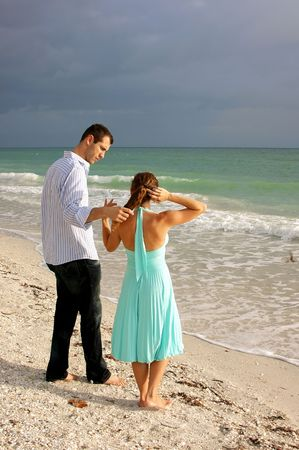 attractive young couple on beach in florida having a discussion with waves crashing in front of them. she is fixing her hair, he appears to be listening photo