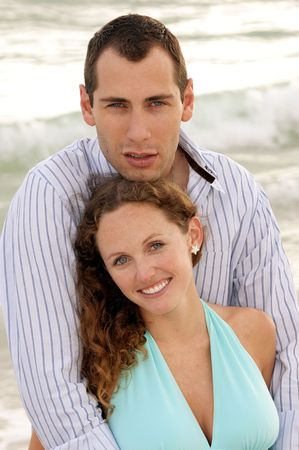 young couple at the beach in the gulf of mexico having a discussion with waves crashing behind them. Stock Photo - 4905048