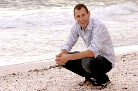 crouches: A casually well dressed smiling young adult crouches at the waters edge at the beach.
