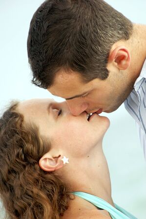 a handsome young man with short hair leans down to kiss a pretty woman with long curly hair
