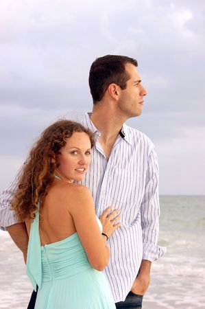 An attractive well dressed young couple  with their bodies facing each other, the man is looking out to the ocean in profile. The wooman is turned and looking at viewer