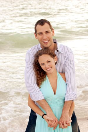 A happy young couple at the beach with man standing behind the woman facing the viewer with arms wrapped around her with waves crashing behind them. Both people are smiling and looking at viewer. photo