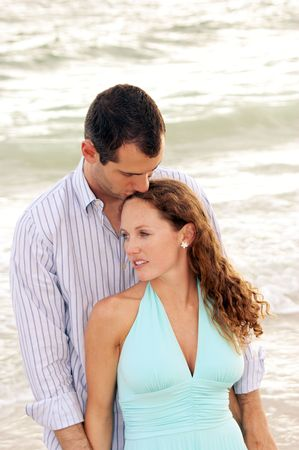 beautiful young couple at the beach, standing facing viewer, man is kissing top of wooman's head, she is leaning into him 免版税图像