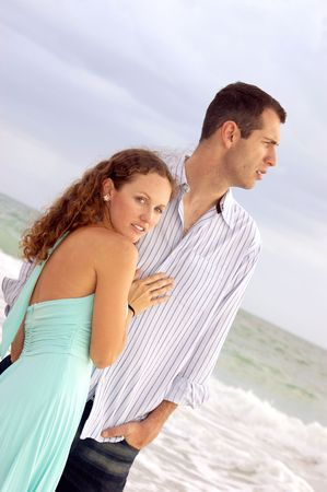 Beautiful dramatic image of young couple on teh sea shore, he is turned profile, she is looking at the viewer, shot at an angle photo
