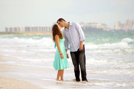 a young couple kissing on the beach with waves crashing behind them and resort buildings, they are standing in the water and look a little wind blown photo