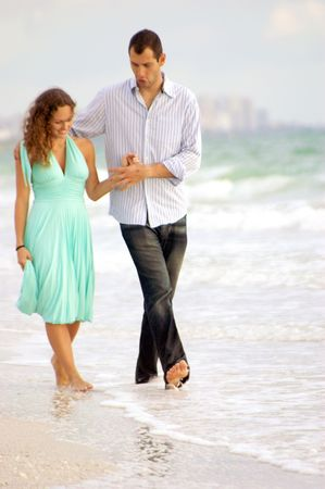 Young happy couple hand in hand skipping through the water at the shore on bonita beach, florida photo