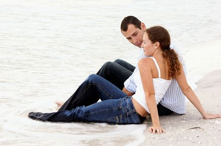 Attractive young couple sitting in the water fully dressed at the beach having a conversation. photo