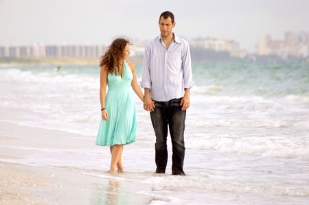 young couple is walking on the beach, they appear to be dissussing their problems or having a serious talk, he looks a little haggard, she is in a pretty dress. photo